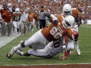 Longhorns defensive tackle Chris Whaley dives over the goal line to score a touchdown against Oklahoma.
